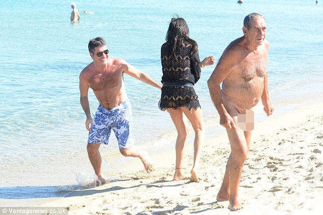 Comedy: Cowell can't believe it as the naturist makes his way across the beach with his manhood on full display