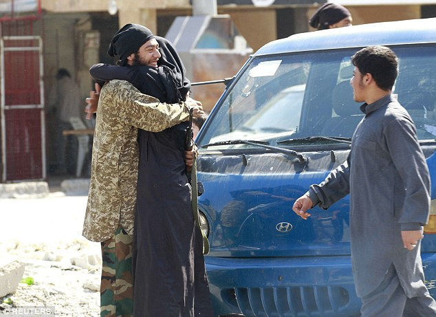 Islamic State militants embrace in celebration after taking over Tabqa air base near Raqqa city on Sunday
