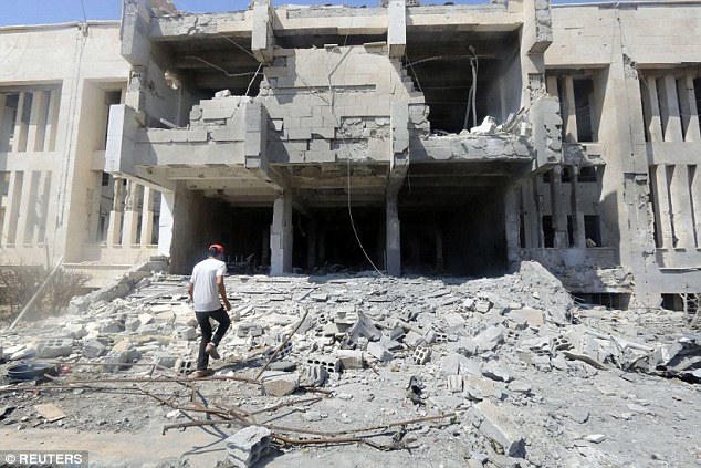 A man inspects damage at the entrance of a Tabqa hospital after a Syrian government air strike