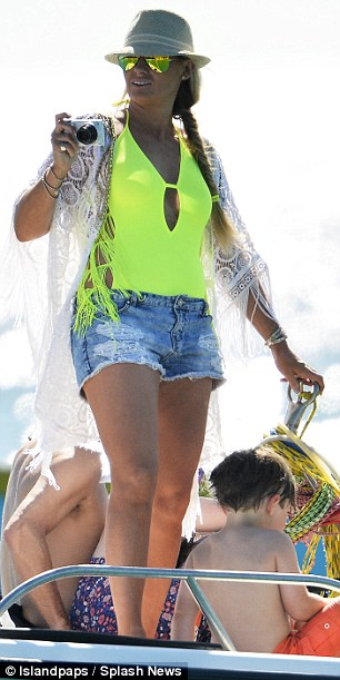Capturing the moment: The television presenter's wifeCarla Germaine stood out from the crowd in her bright look (L)