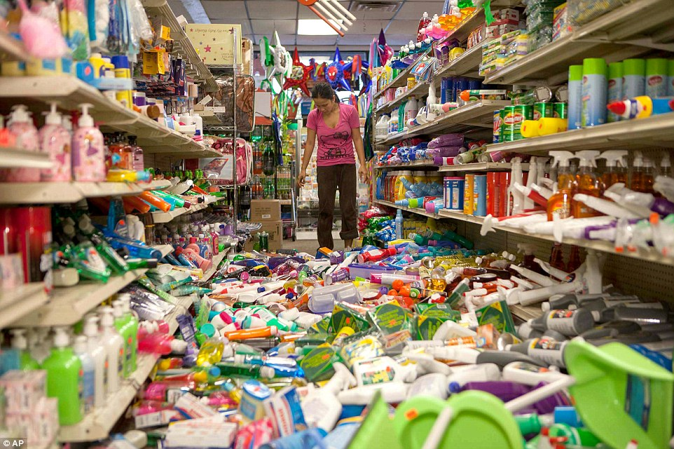 Nina Quidit cleans up the Dollar Plus and Party Supplies Store in American Canyon Calif. after an earthquake on Sunday Aug. 24, 2014.