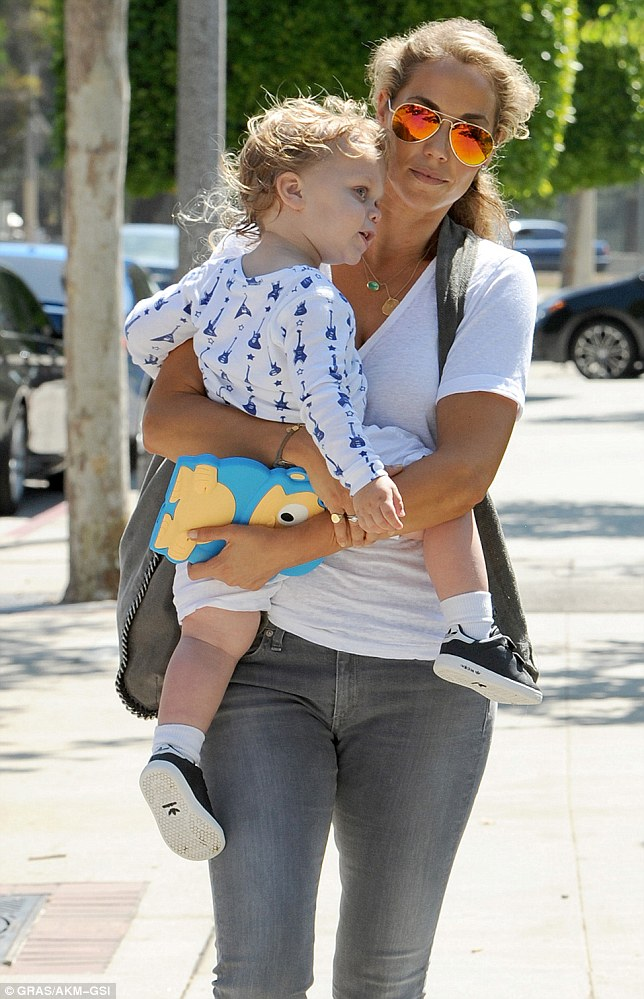 Muscle-mum: Elizabeth Berkley carried son Sky to a breakfast date on Saturday in their local neighbourhood of Brentwood, California