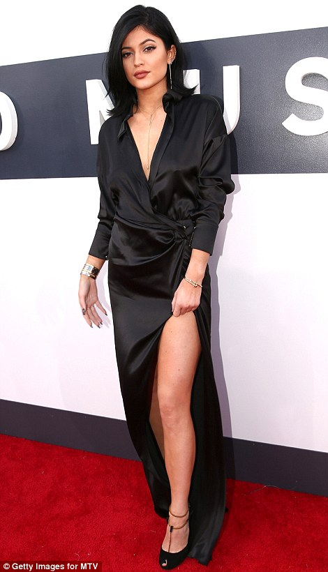 Going vamp: While Kylie opted for silky black wrap dress, Kendall wore a sheer black top and black trousers that accentuated her tiny waist
