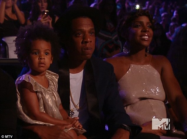 Like family: Kelly watches her former bandmate Beyonce's performance next to the singer's husband rapper Jay Z and their daughter Blue Ivy, aged two
