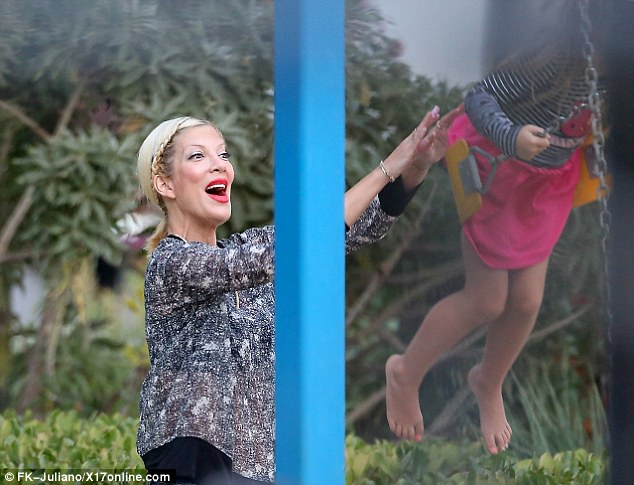 Higher, Mommy, higher! The six-year-old went barefoot on the play equipment in a pink skirt and black and white striped top with pink sequinned cat design as her mom diligently pushed her