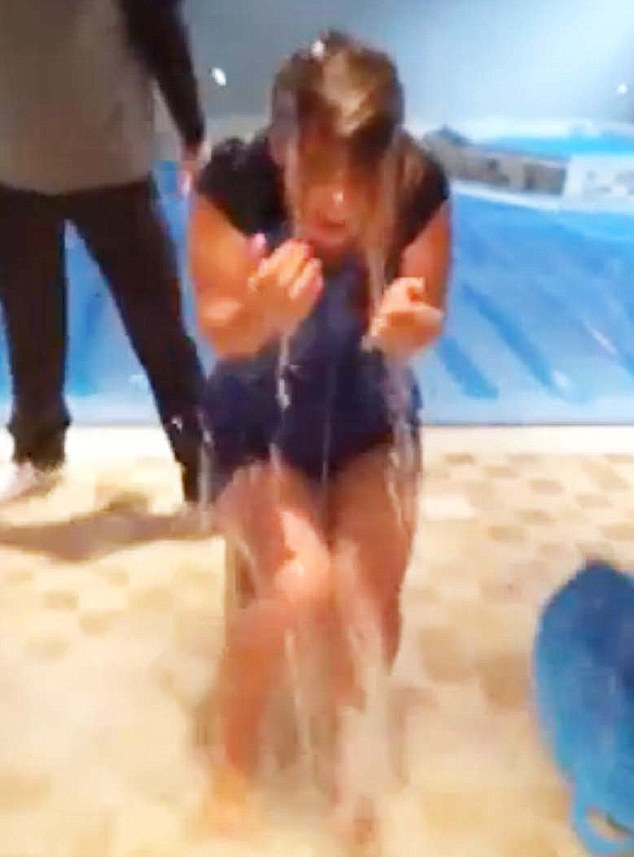 Water Wag: Coleen Rooney is wet through, as husband Wayne lurks in the background