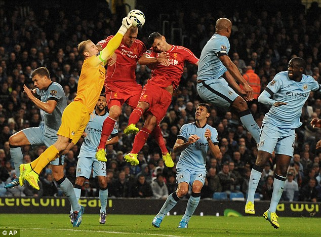 Commanding: Hart comes out to punch the ball clear under pressure in Manchester City's 3-1 win over Liverpool on Monday night