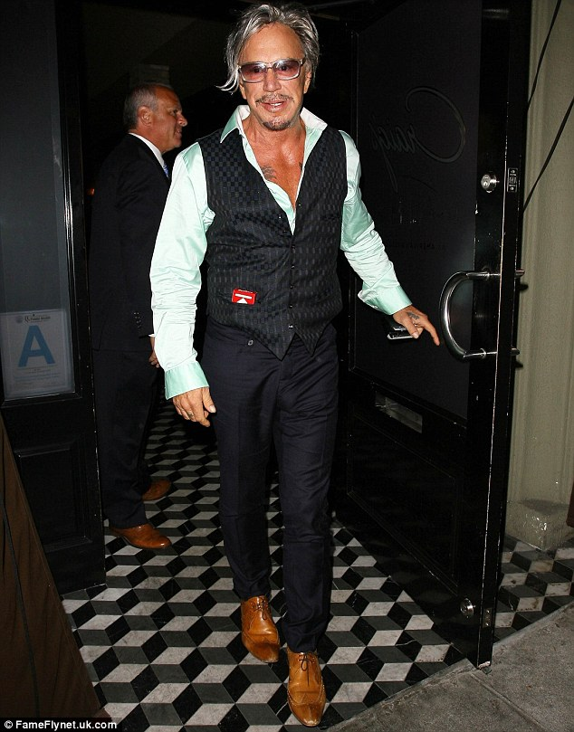 Silver fox: Mickey Rourke, 61, shows off his toned bronzed chest in an open shirt as he leaves Craig's restaurant in West Hollywood on Monday
