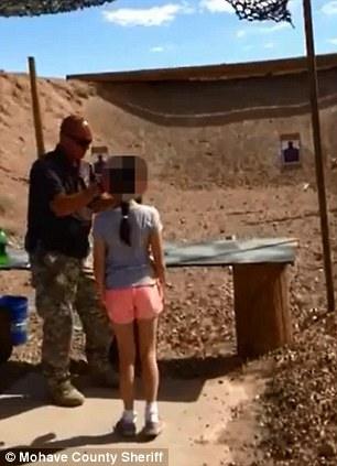 Instructions: Charles Vacca, a father and veteran from Lake Havasu City, Arizona, teaches the 9-year-old girl how to handle the Uzi