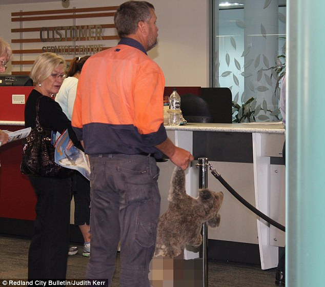 A concerned woman watches on as Mr Mewett waits patiently in the customer service queue at Redland City Council.