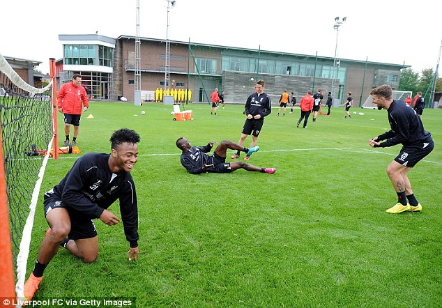 Floored genius: Balotelli, on the deck, Raheem Sterling, Fabio Borini and Co share a laugh at training
