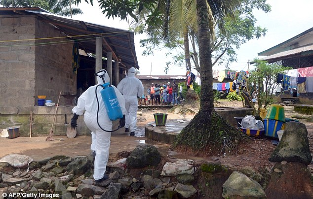 Grisly task: Two nurses in protective suits enter a Liberian village to search for locals who have fallen ill