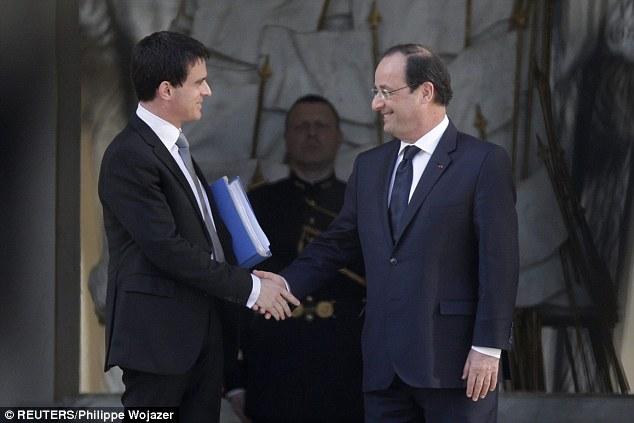 Prime Minister Manuel Valls (left) shakes hands with President Francois Hollande