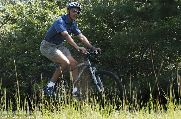 Frumpy indeed: Is this an over-sized Boy Scout? No, it's the most powerful man in the world, taking a bike ride