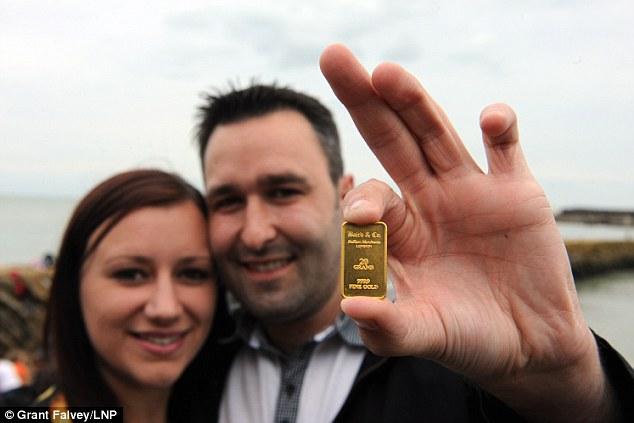 © Licensed to London News Pictures. 30/08/2014 Kirsty Henderson age 26 and Kevin Wood age 28 from Canterbury are the finders of the first declared gold bar in Folkestone,Kent.  Folkestone Gold Beach. £10,000 of buried treasure at Outer Harbour beach near Sunny Sands, Folkestone,Kent. The installation, entitled ìFolkestone Digsî, is funded by Bristol-based designers Situations and the idea for the project came from Berlin-based artist Michael Sailstorfer. The small gold bars - similar to a dog tag - come in two sizes, worth around £250 and £500. (Byline:Grant Falvey/LNP)