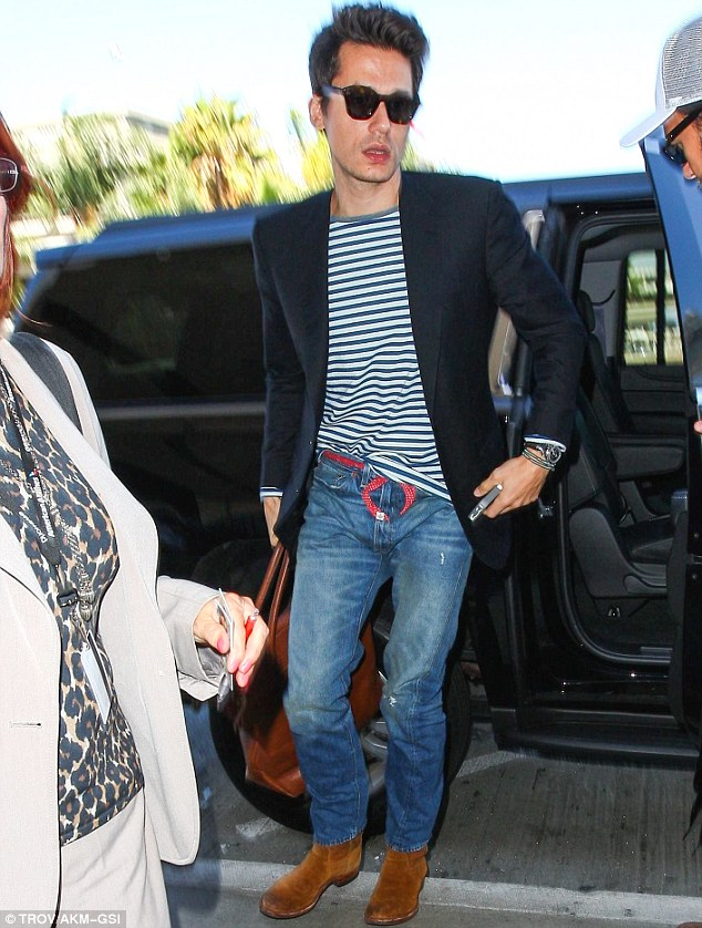 Free flyin': The musician accessorised with a large brown leather overnight bag and tortoiseshell wayfarer sunglasses as he made his way through the international airport