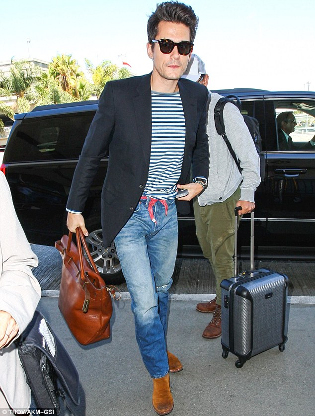 Fashionable flyer: The Your Body Is A Wonderland singer fiddled with his blue and white striped tee, tucking it into his light blue denim trousers featuring a red tie-up belt, paired with a black blazer and suede boots