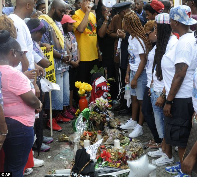 Tribute: Family members of Michael Brown, have a moment of silence at the site of the shooting in Ferguson