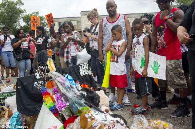 Reflection: Protesters including young children look at a memorial marking the location where Michael Brown was killed