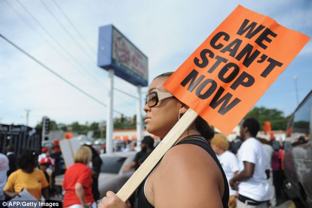 Community: A woman holds a sign encouraging people to keep protesting for justice for Michael Brown