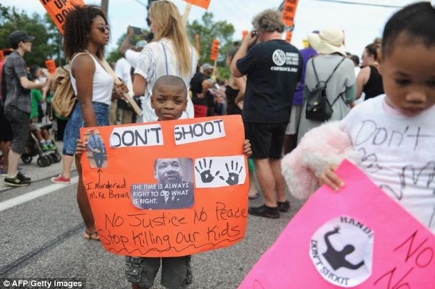 Children: Two little children hold up signs asking the police 'to stop killing our kids' at the march in Ferguson