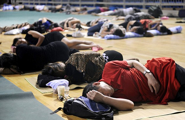 Rough night: Parents desperate to stay with their children but cannot afford a room close to the university campus bed down on the gym floor using rucksacks and towels for pillows