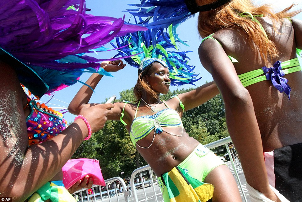 Dressed for the occasion: Adjee Hamilton, center, dances as she and others wait to take part in the West Indian Day Parade