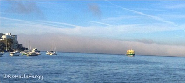 A rolling fog stretches across the horizon behind a ferry on the harbour