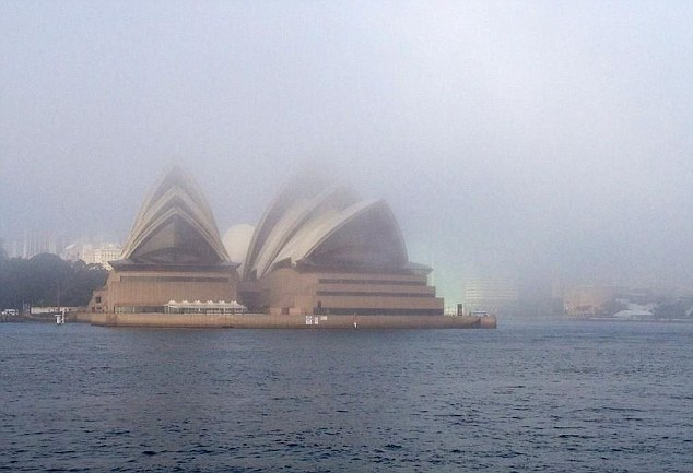The opera house is more visible as the fog starts to clear