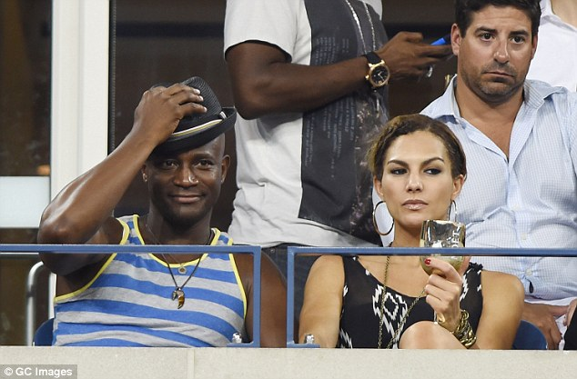 Hats off: Taye Diggs looked cool in striped shirt and black hat as he enjoyed the show with model girlfriend Amanza Smith Brown