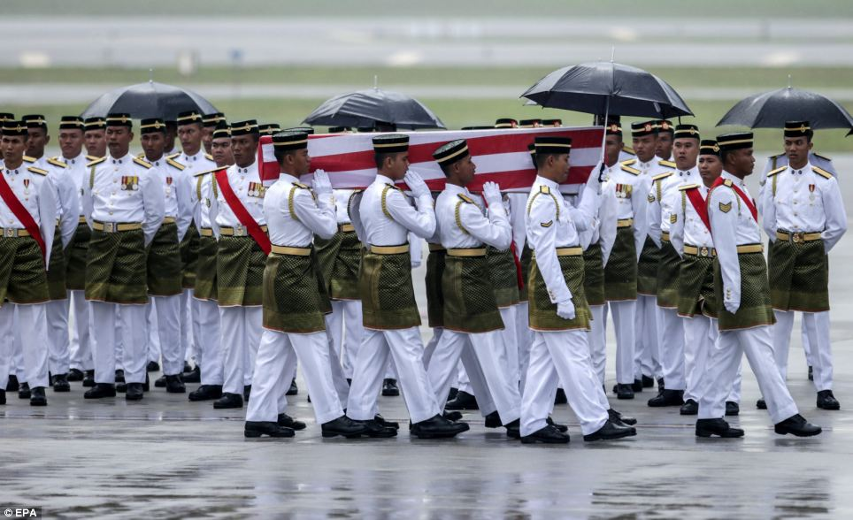 Military-style: Royal Malay Regiment army personnel are pictured carrying a coffin to a hearse during the arrival ceremony at Kuala Lumpur International airport