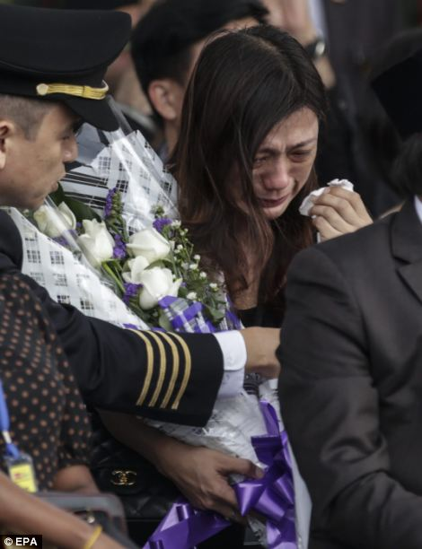 The wife of Malaysia Airlines flight MH17 pilot Captain Eugene Choo, who was killed in the MH17 plane crash, cries during the arrival ceremony of Malaysia Airlines MH17 victims at the Kuala Lumpur International airport in Sepang