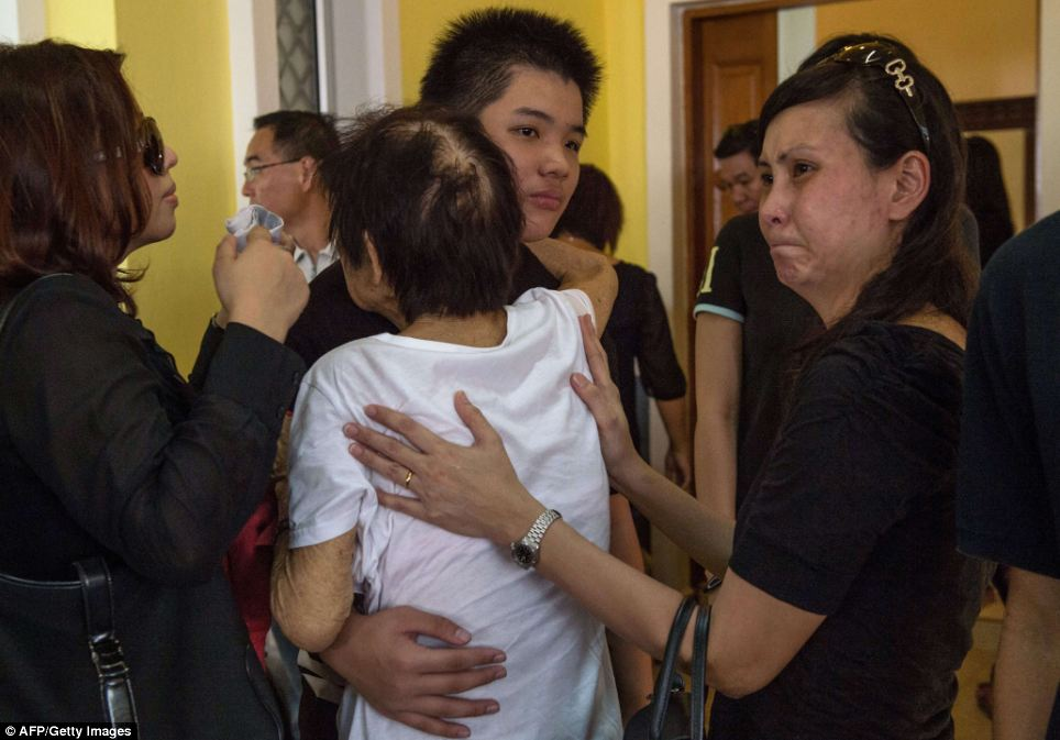 Comfort: Melvic hugs his grandmother Chew Lai Choo during the service for Captain Choo, who was killed alongside Captain Amran when MH17 was gunned down