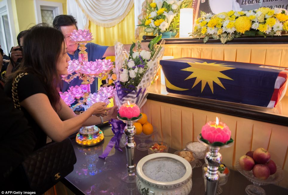 Colourful: Ms Loi places flowers near Captain Choo's urn, which was placed on a raised surface at his residence in Seremban, around 46 miles from Kuala Lumpur