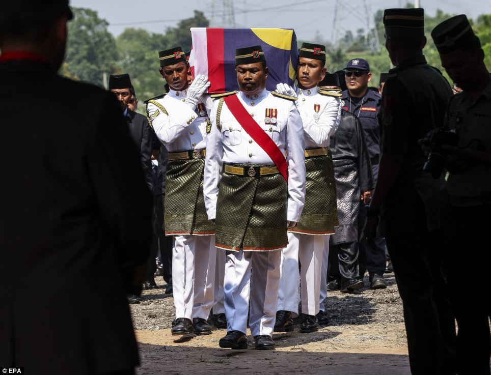 A special ceremony: Draped in a Malaysian flag, the body of Captain Wan Amran is pictured being carried by soldiers into Shah Alam, 15 miles west of Kuala Lumpur