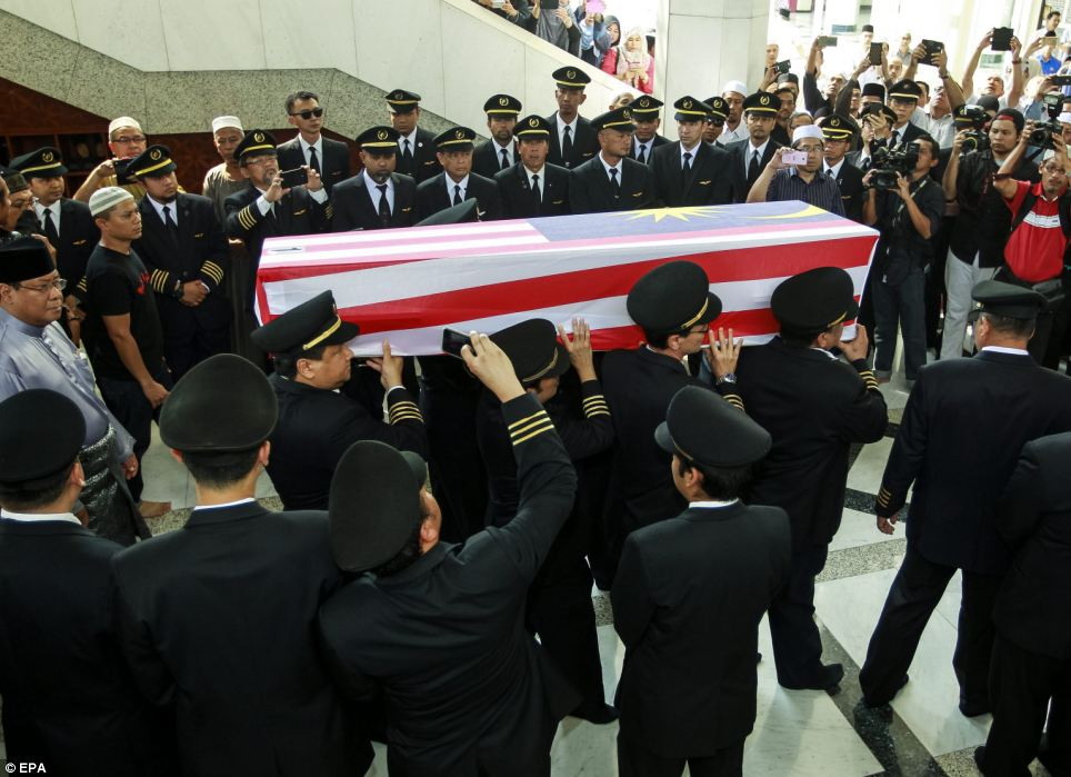 Colleagues: The pilot's body was carried by members of the Royal Malay Regiment army, before it was passed onto his colleagues, other Malaysian Airlines pilots