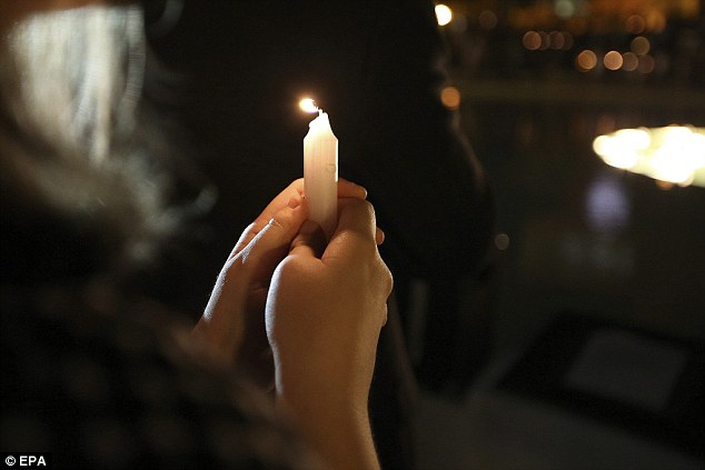 A student at UCF holds a candle during a vigil for freelance journalist Steven Sotloff yesterday evening