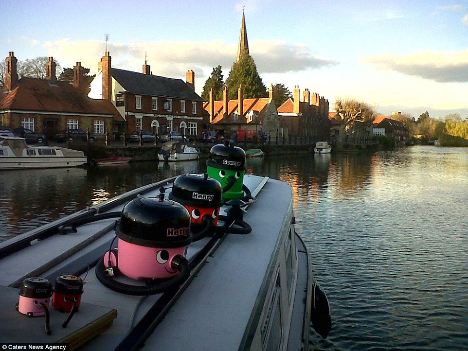 Danny Walker, 28, was bored of vacuuming his home in Abingdon, Oxford, so decided to capture his family of Henry vacuum cleaners engaging in a range of daily activities. Above, Henry, Hettie, George and two 'baby' vacuum cleaners are pictured relaxing on the roof of a boat as it cruises down a canal in the market town