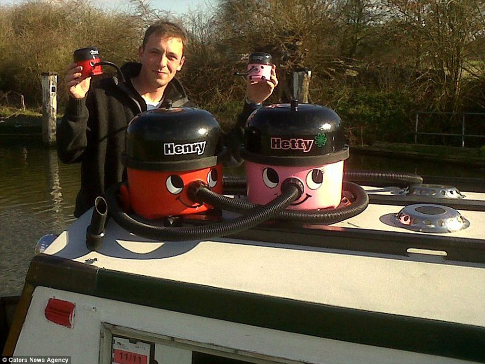 Creative father: Mr Walker, who works at a brewery, is pictured posing with Henry, Hetty and the 'baby' vacuum cleaners on the roof of a boat on the canal in Abingdon