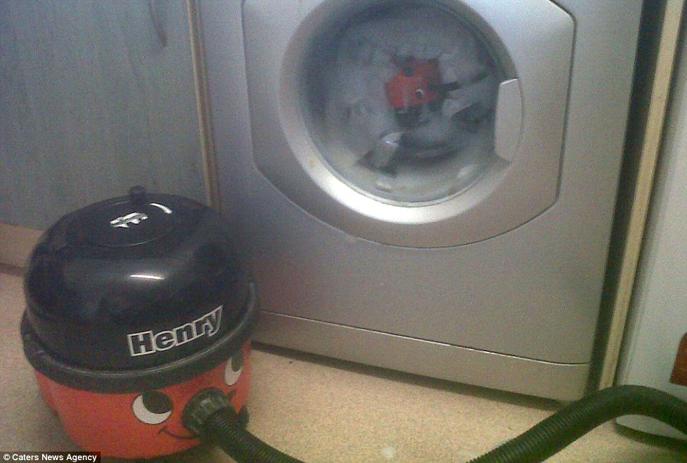 Oh no! Mr Walker said: 'It's a fun way to brighten up people's days and I love getting out and about. Above, Henry accidentally puts a 'baby' hoover in the washing machine