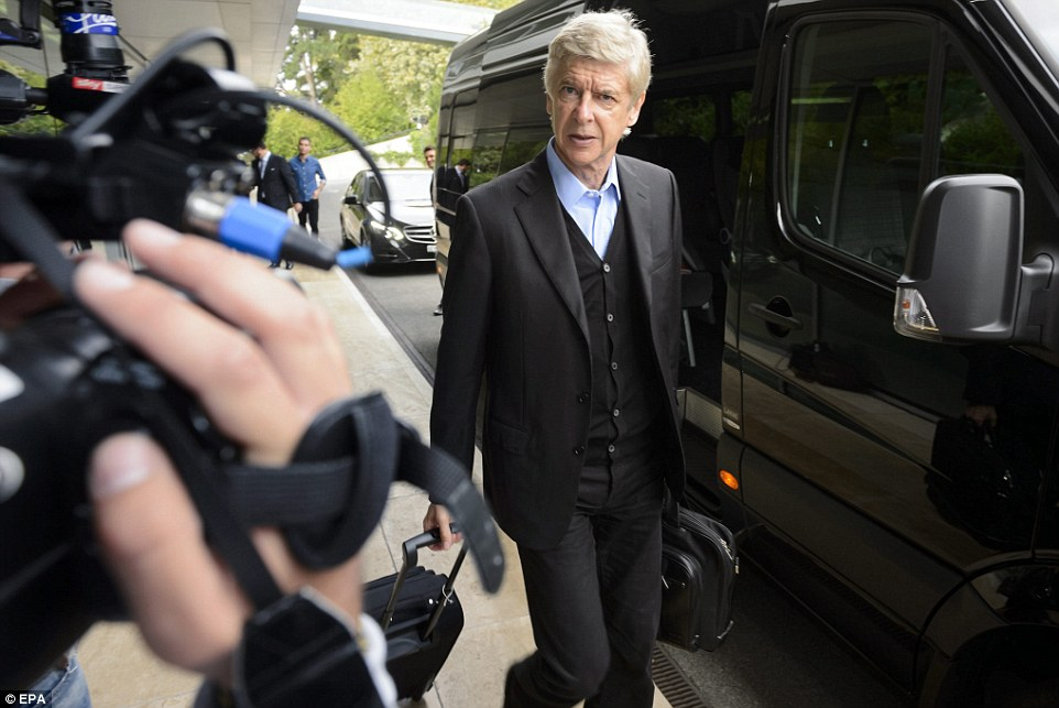 Annual meeting: Arsenal manager Wenger looks on as the press wait outside the UEFA headquarters