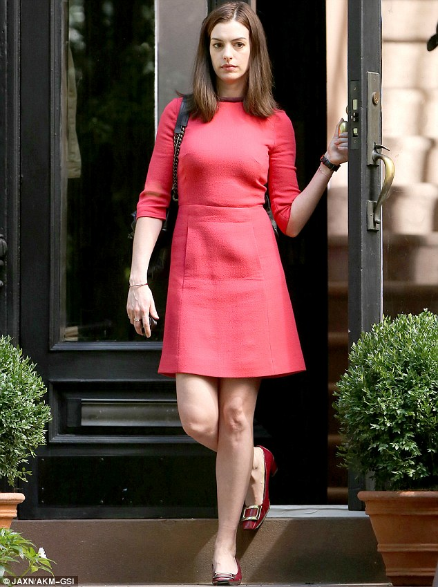 Different look: Anne Hathaway, 31, looked chic in a bright red Sixties style dress while filming The Intern in New York on Thursday