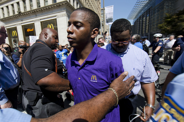 A McDonald's worker is detained by police during a protest to push fast-food chains to pay their employees at least $15 an hour, outside a McDonald's restaurant today in Philadelphia