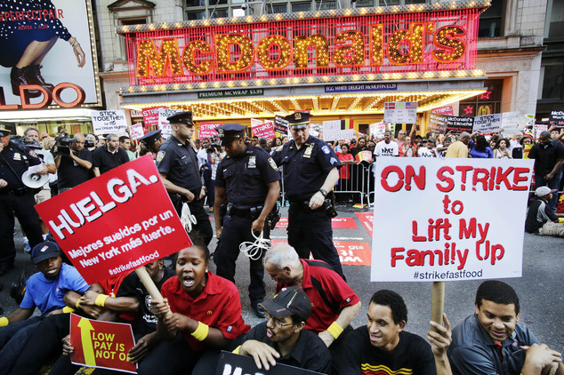 Protesters sit in front of a McDonald's restaurant on 42nd Street in New York's Times Square as police officers move in to begin making arrests. A day of planned protests were taking place in 150 cities across the country by workers from fast-food chains