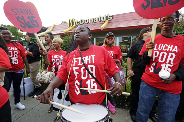 Carmalita Johnson drums as protesters participate in a rally outside a McDonald's on Chicago's south side as labor organizers escalate their campaign to unionize the industry's workers