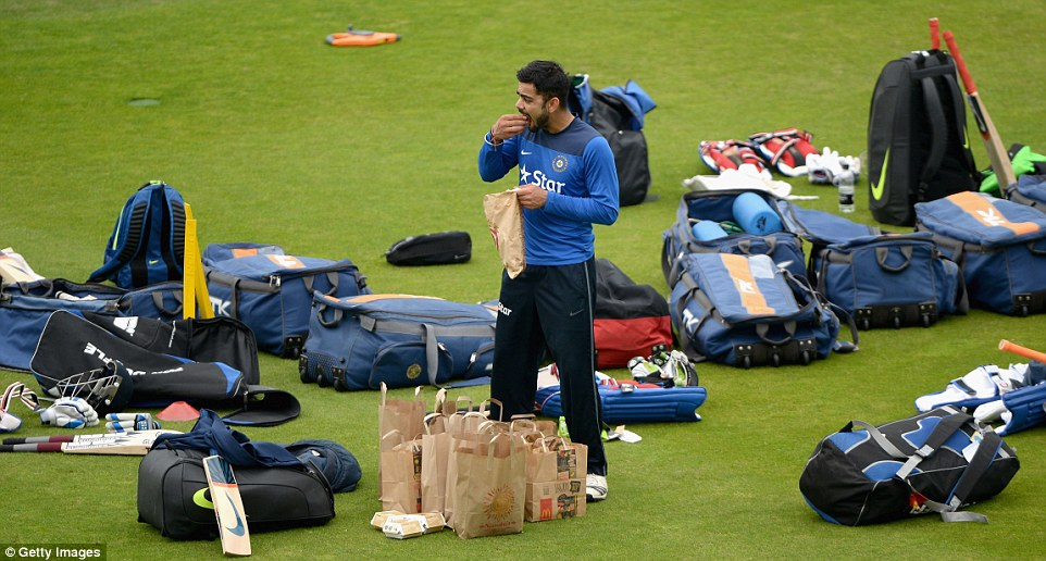 Tucking in: India's marquee batsman Virat Kohli scoffs down some fast food on the Headingley outfield during a nets session