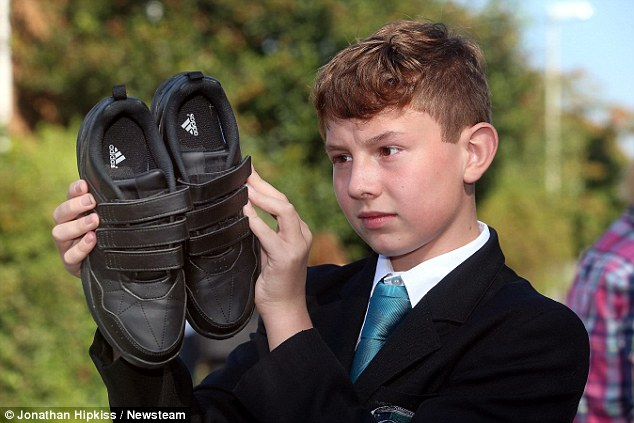Sole responsibility: The Coseley School sent one hundred students home because of incorrect footwear. Pictured here is Lewis Guthrie, 12, with his shoes that the school say are not accepted