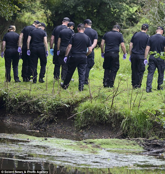 Dozens of police officers searched a river today for a murder weapon just yards from where she stabbed