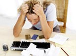 Woman stressed at a computer keyboard paper work credit cards cyber-bullying ROYALTY FREE