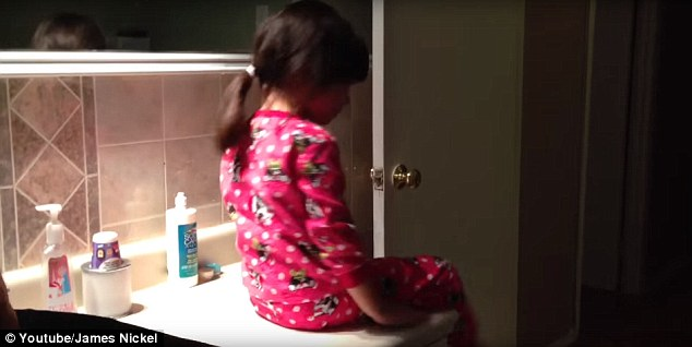 Easy: The clever dad wrapped his daughter's hair tie around the vacuum cleaner pipe, before sucking her hair up and swiftly popping the tie on
